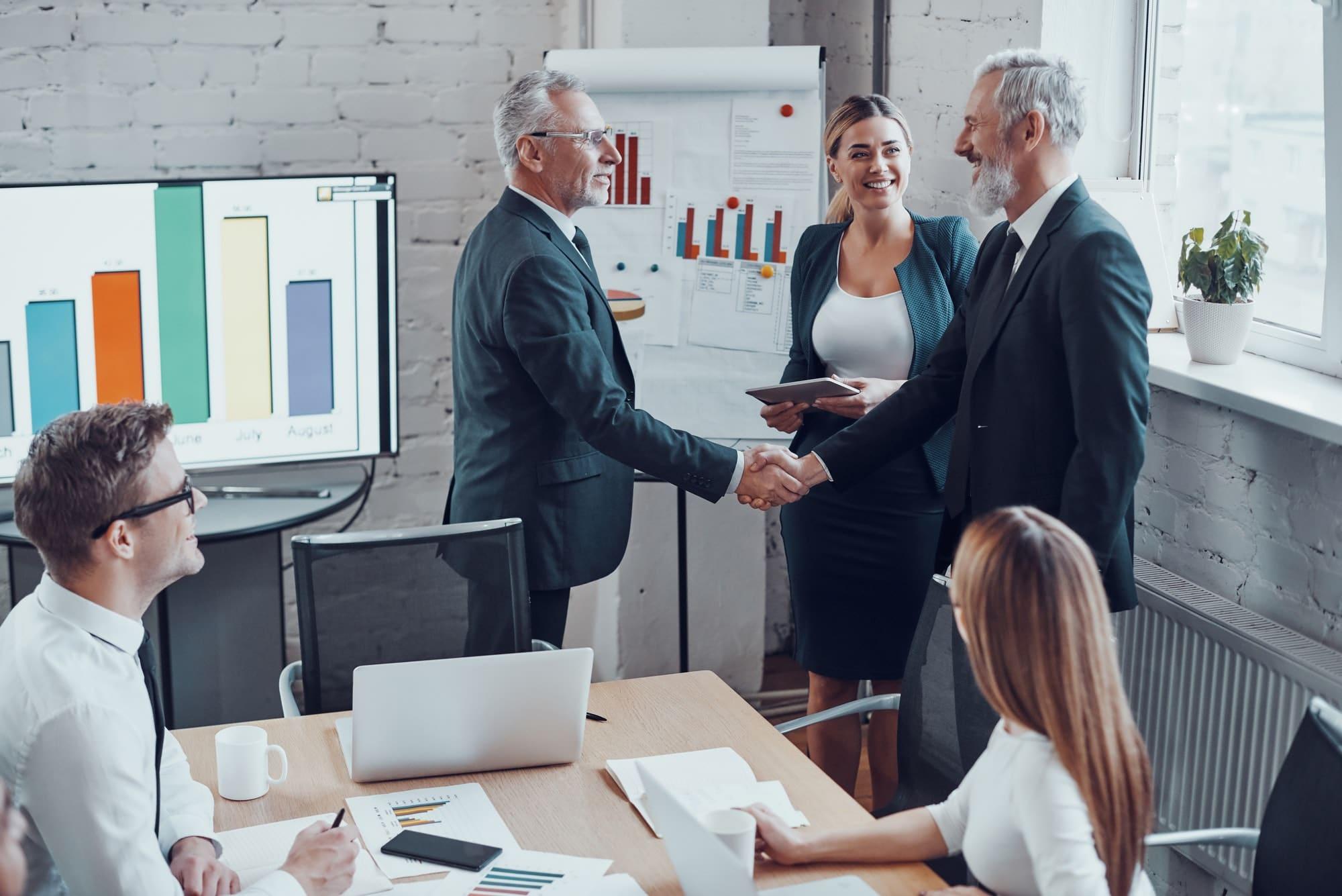 Confident businessmen shaking hands