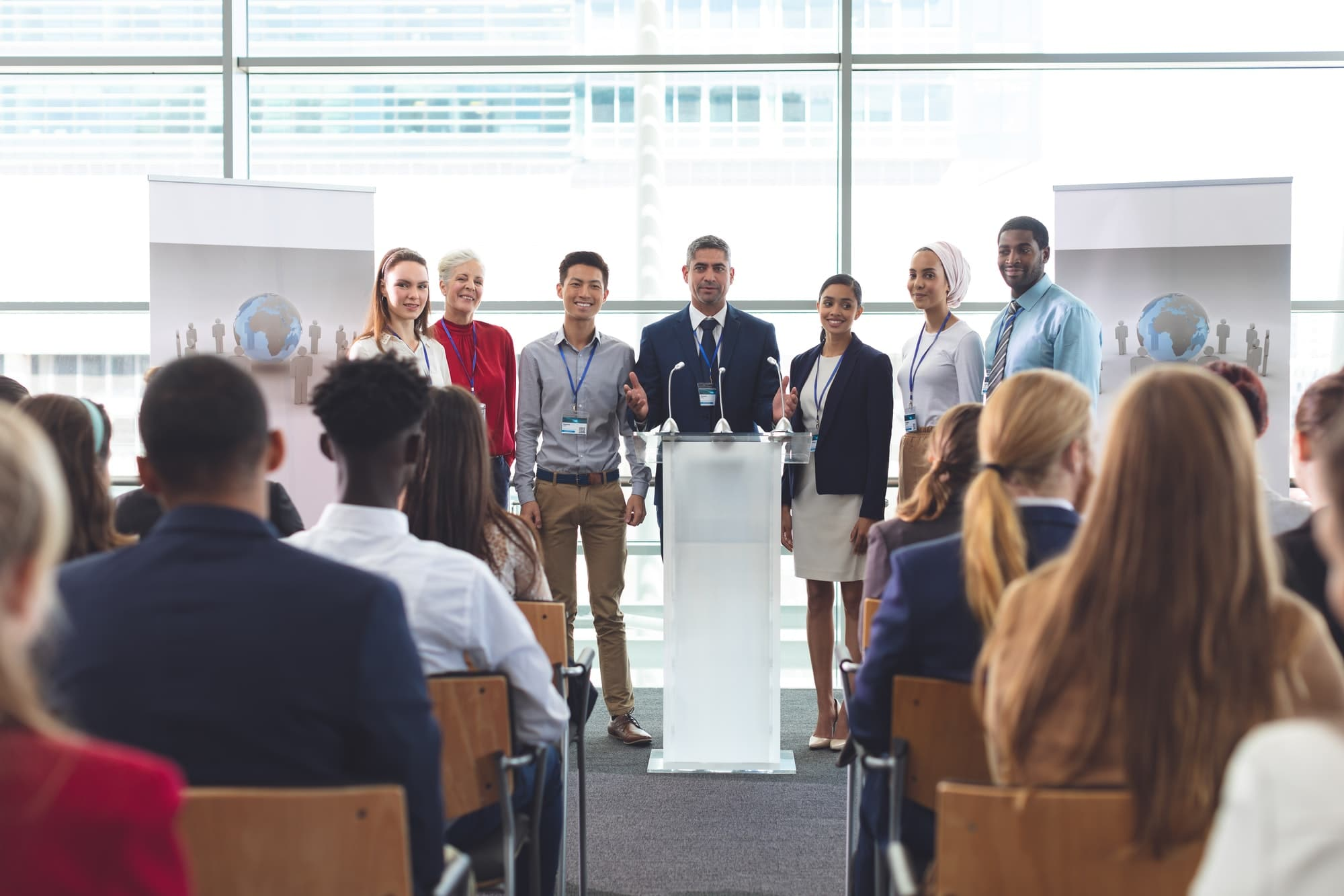 Diverse group of business people standing on podium while speaking at business seminar