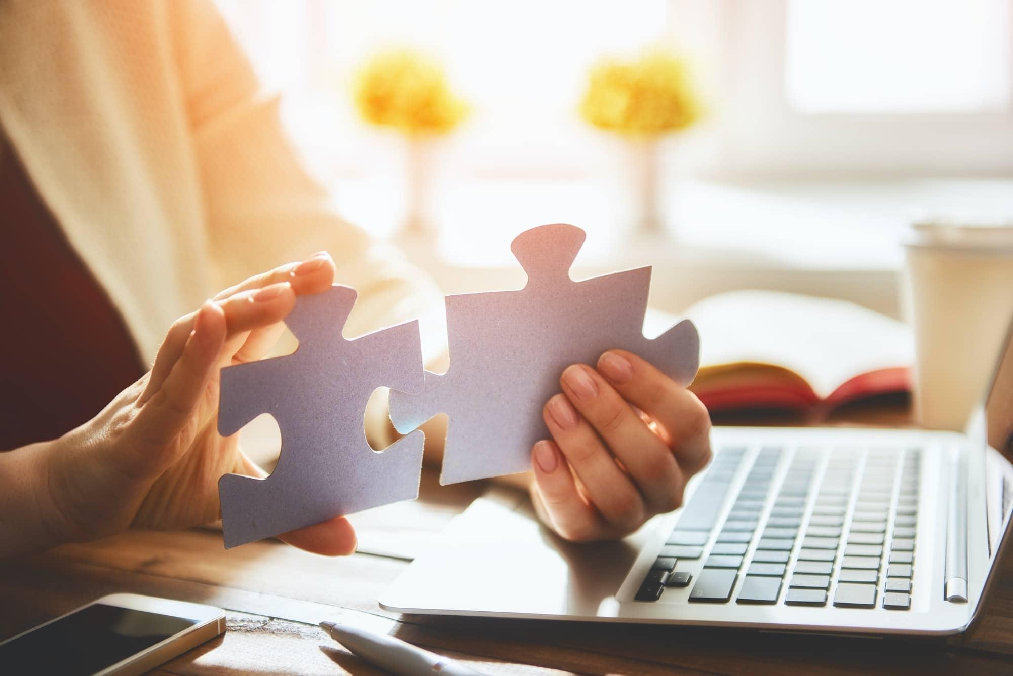 Woman connects couple puzzle piece