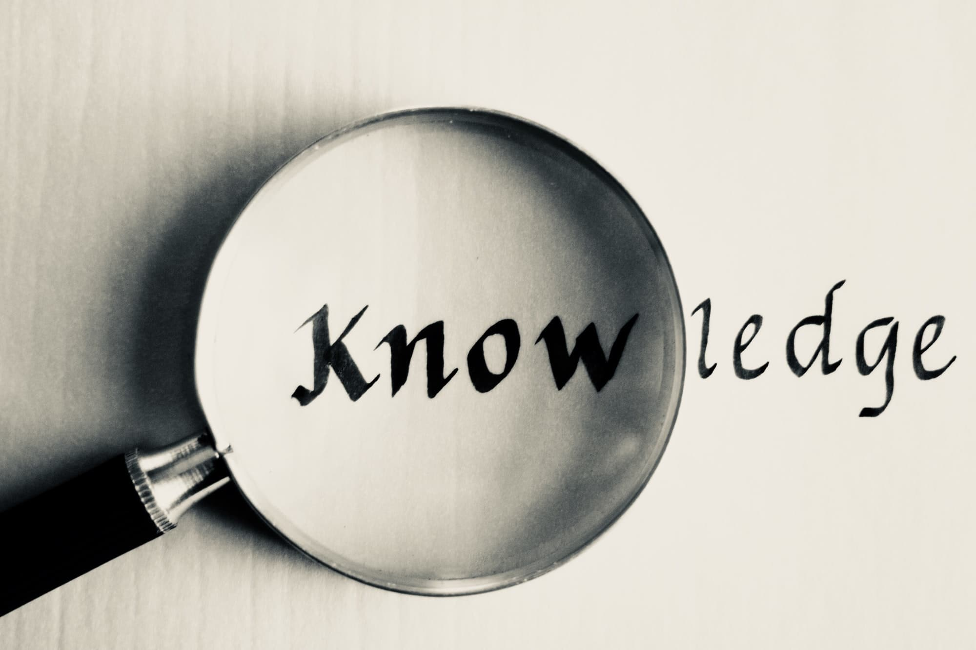 """A vintage magnifying glass emphasizing the """"Know"""" part of the word """"Knowledge"""" on parchment paper"""