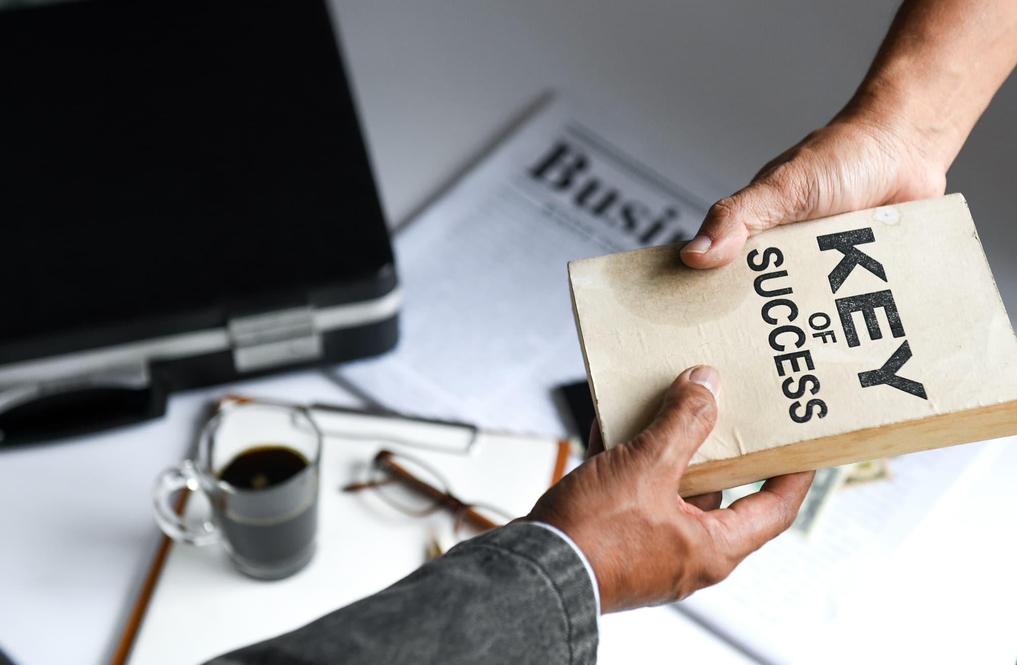 Businessmen deliver key of success book,Business concepts.