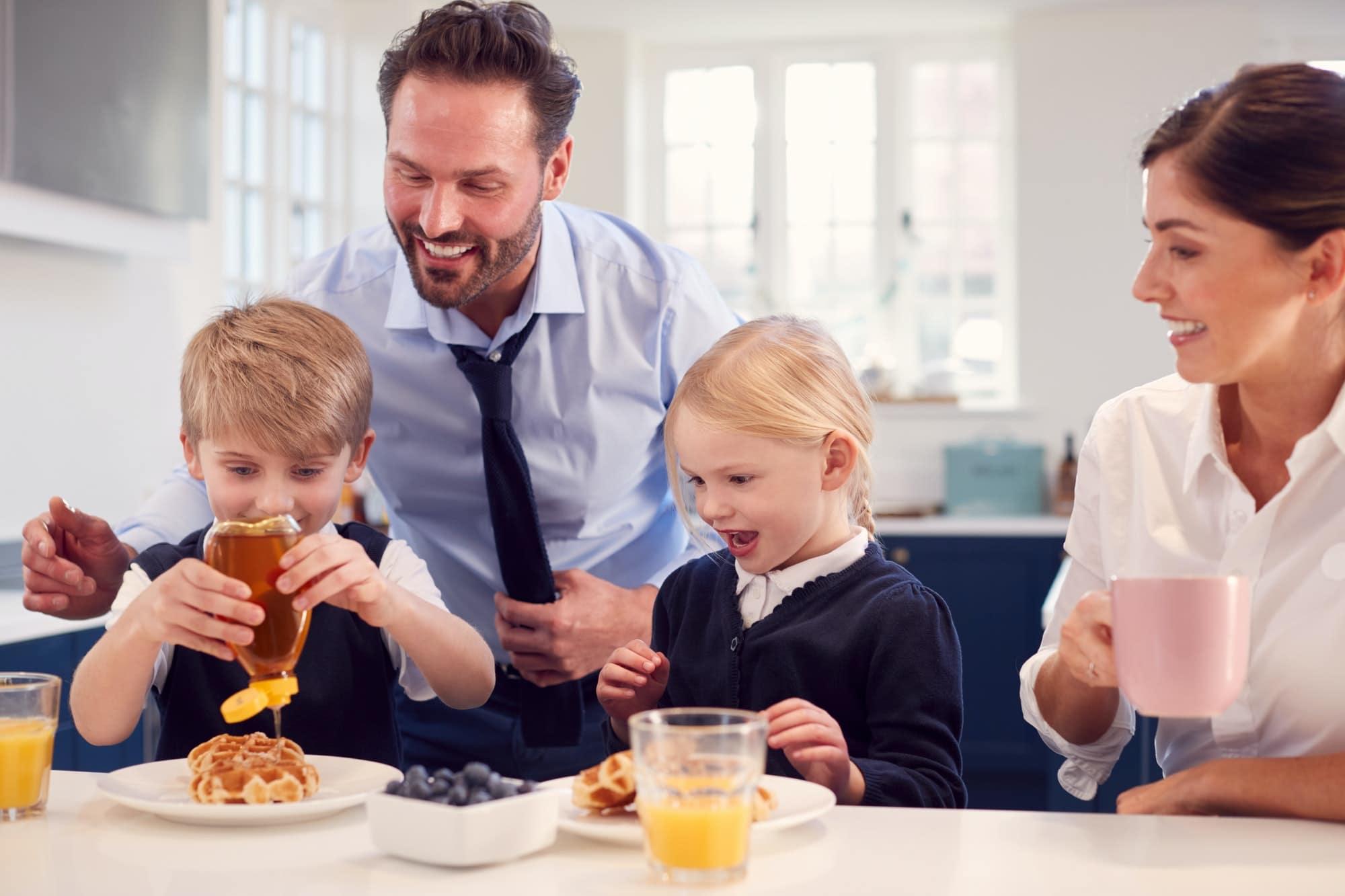 Children Wearing School Uniform In Kitchen Eating Breakfast Waffles As Parents Get Ready For Work