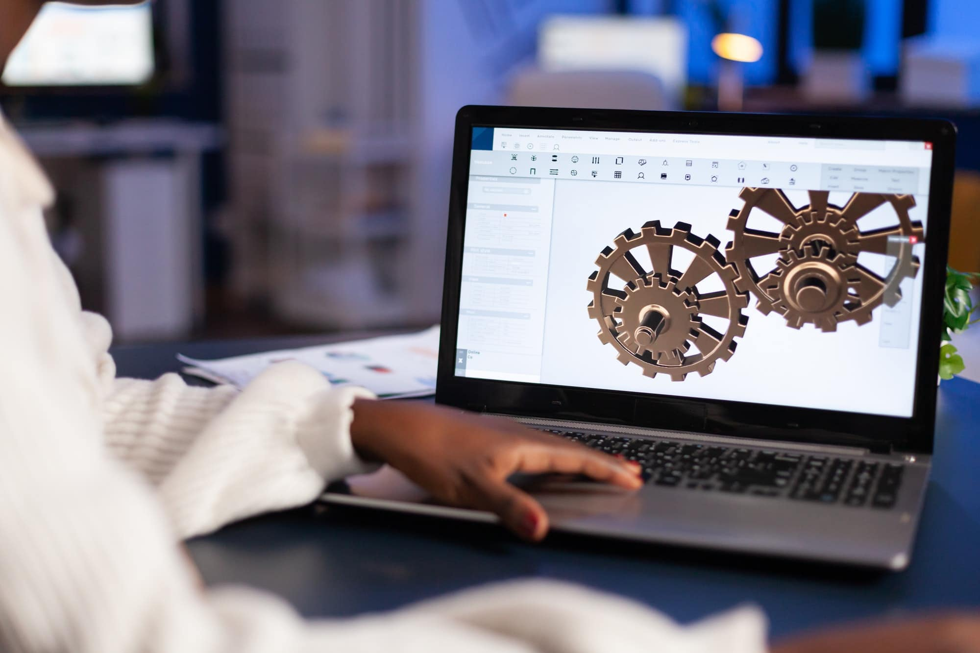 Close up of mechanical gears while engineer working with software