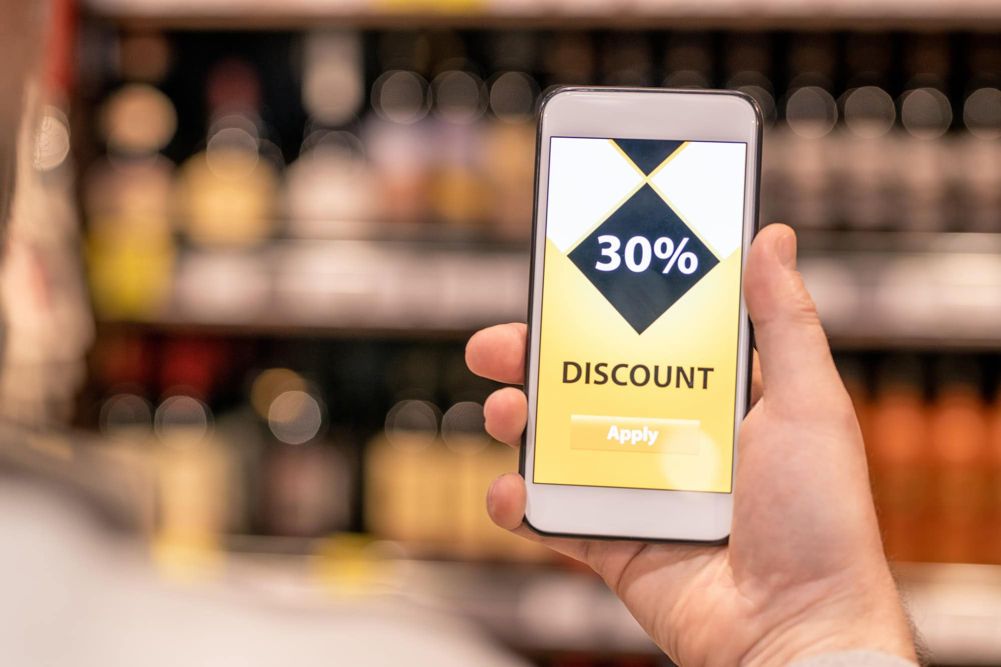 Hand of contemporary aged male customer with smartphone using discount