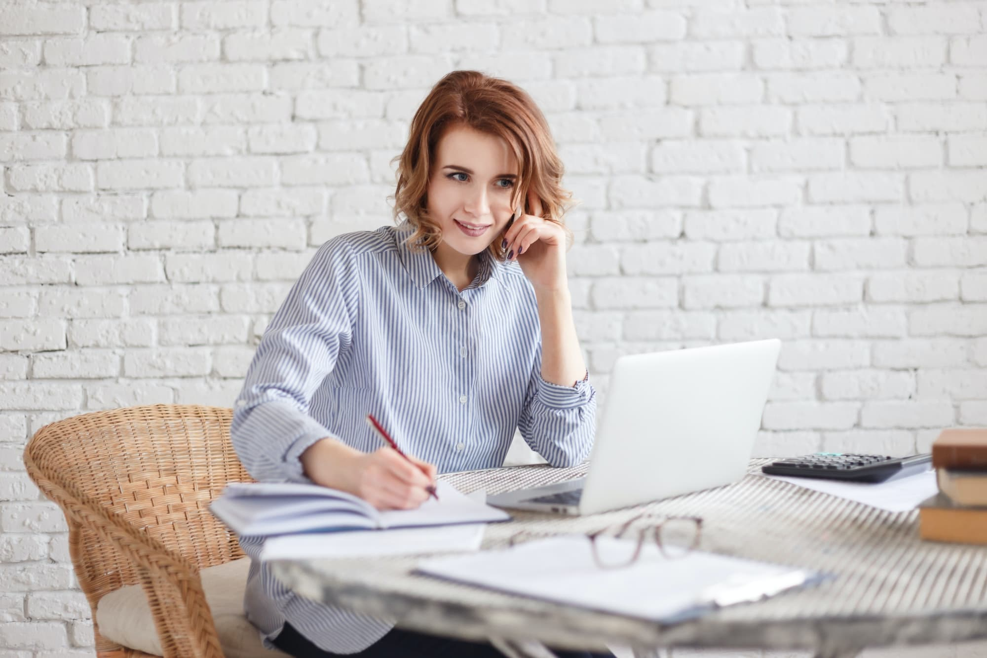 Happy smiling woman freelancer writes notes in a diary sitting in a office or at home.