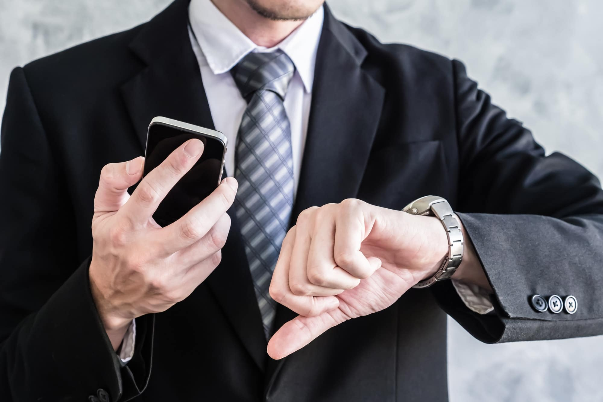 Close up of businessman using smart phone and checking time on his wrist watch.